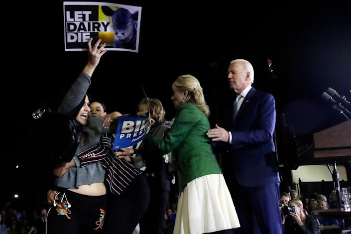 A protester at left, is held back by Biden adviser Symone Sanders, wearing stripes, face unseen, and Jill Biden, second from right, as Democratic presidential candidate former Vice President Joe Biden stands, at right, during a primary election night rally, Tuesday, March 3, 2020, in Los Angeles. (AP Photo/Marcio Jose Sanchez)