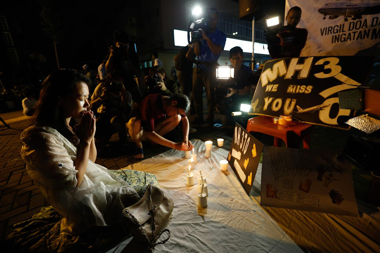Kelly Wen, wife of Chinese passenger aboard the missing Malaysia Airlines Flight MH370 prays during an event to mark one year anniversary of the plane disappearance, during a candlelight vigil for passengers onboard the missing Malaysia Airlines Flight MH370 in Kuala Lumpur, Malaysia, on Friday, March 6, 2015. (AP Photo/Vincent Thian)