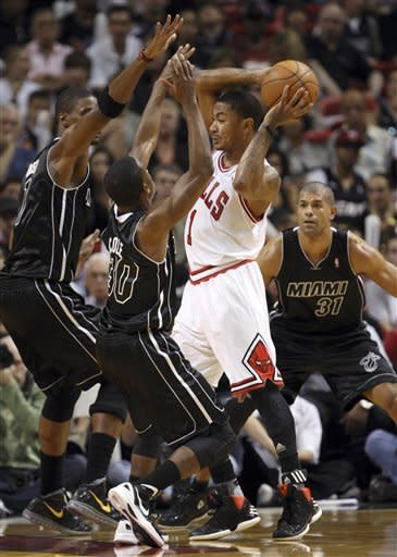 Chicago Bulls guard Derrick Rose, second from right, looks for an opening past Miami Heat forward Chris Bosh, left, guard Norris Cole, second from left, and forward Shane Battier (31) during the first half of an NBA basketball game, Sunday, Jan. 29, 2012, in Miami. (AP Photo/Wilfredo Lee)