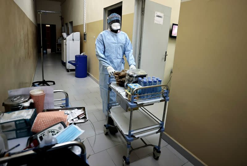 Abdoulaye Ndour, a member of the medical staff pushes the cart as he is about to distribute dinner to patients suffering from the coronavirus disease (COVID-19) at the infectious diseases department of the the University Hospital Fann, in Dakar