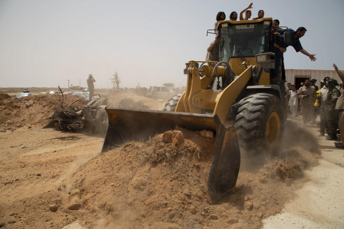 A bulldozer pushes earth to during a ceremony to reopen the road between the cities of Misrata and Sirte Sunday, June 20, 2021. Libya's interim authorities reopened on Sunday the Mediterranean coastal highway linking the country's long-divided eastern and western cities, in the latest bid to reunite the territories after years of civil war. (AP Photo/Yousef Murad)