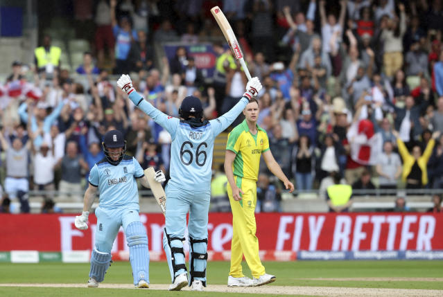 England's captain Eoin Morgan, left, celebrates with teammate Joe Root after winning the Cricket World Cup semi-final match between Australia and England at Edgbaston in Birmingham, England, Thursday, July 11, 2019. England beat Australia by 8 wickets with 107 balls remaining. (AP Photo/Rui Vieira)