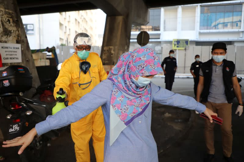 A worker sprays disinfectant on a woman during the movement control order due to the outbreak of the coronavirus disease (COVID-19), in Kuala Lumpur