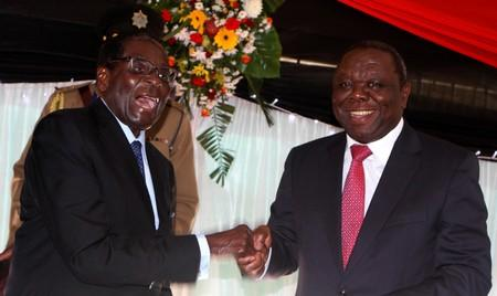 FILE PHOTO: Zimbabwe President Robert Mugabe jokes with Prime Minister Morgan Tsvangirai after signing Zimbabwe's new constitution into law in the capital Harare