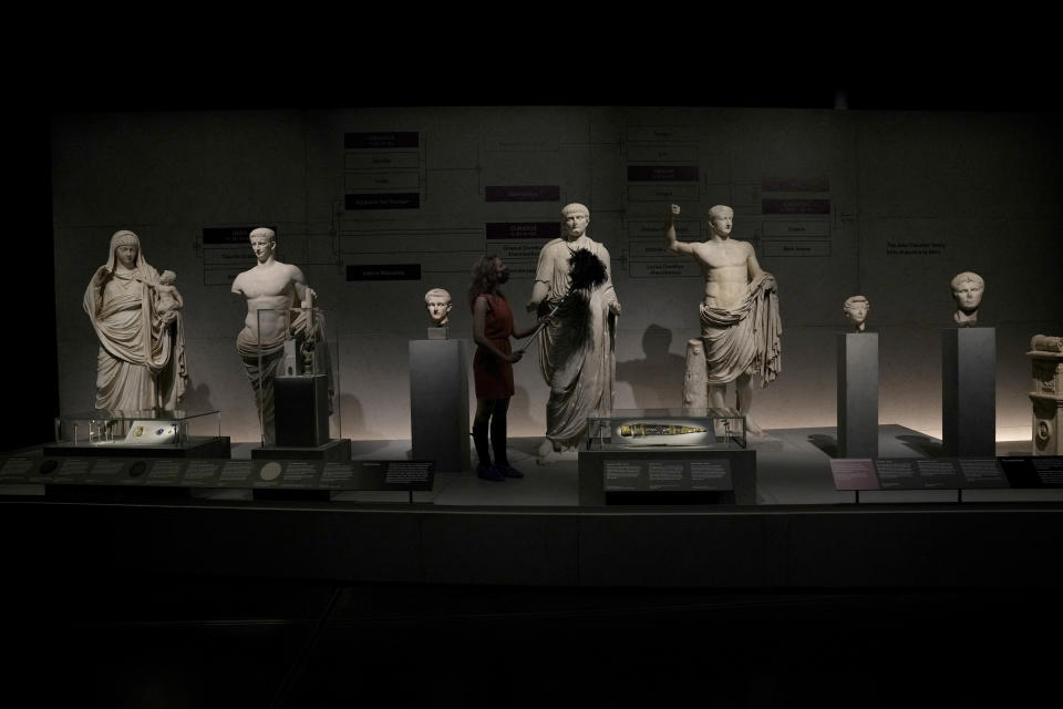 """A museum employee poses for photographers with statues of members of the Julio-Claudian family which was from the first Roman emperor Augustus descending to Nero the last in the line, during a media preview for the """"Nero: the man behind the myth"""" exhibition, at the British Museum in London, Monday, May 24, 2021. The exhibition, which open to visitors on May 27 and runs until October 24, explores the true story of Rome's fifth emperor informed by new research and archaeological evidence from the time. (AP Photo/Matt Dunham)"""