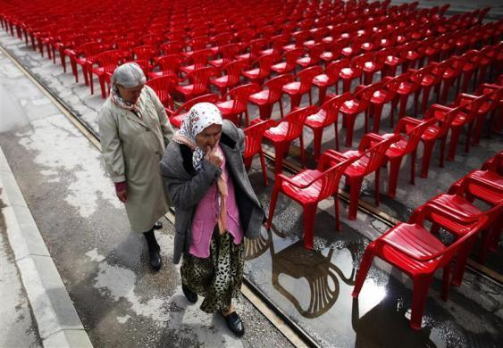 Women walk past some of the 11,541 red chairs along Titova street in Sarajevo, as the city marks the 20th anniversary of the start of the Bosnian war, April 6, 2012. The anniversary finds the Balkan country still deeply divided, power shared between Serbs, Croats and Muslims in a single state ruled by ethnic quotas and united by the weakest of central governments.