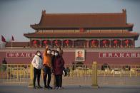 Visitors wearing masks take selfies in front of the Tiananmen Gate, as the country is hit by an epidemic of the new coronavirus, in Beijing