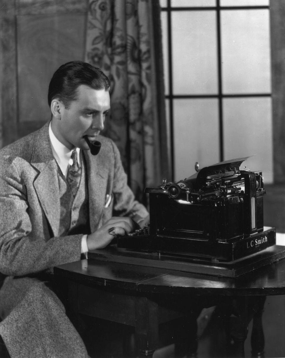 <p>A man smokes a pipe while doing work on a typewriter, wearing a three-piece tweed suit. While this definitely looks like a scene out of an old movie, smoking was permitted in office settings until it was banned starting in the 1990's. </p>