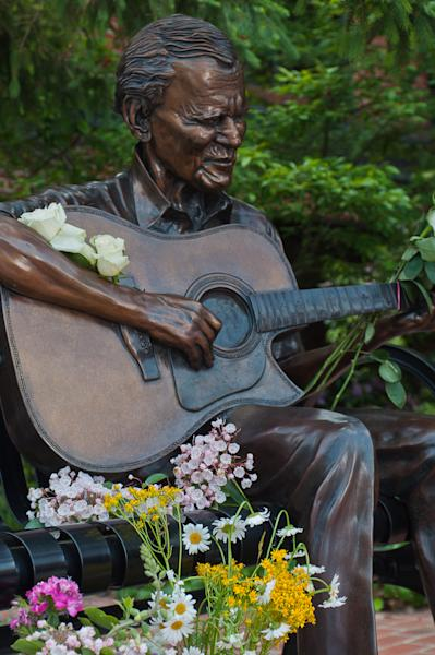 "In this photo provided by Mast General Store, flowers adorn a statue of Arthel ""Doc"" Watson in downtown Boone, N.C., on Friday, May 25, 2012. The Grammy-winning folk musician Doc Watson is in critical condition but improving at a North Carolina hospital after colon surgery. (AP Photo/Mast General Store, Lynn Willis)"