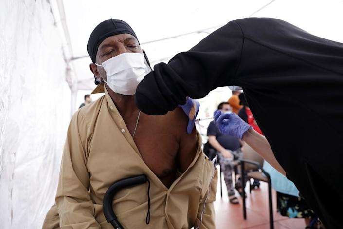 James Smith, 64, of Los Angeles, left, gets vaccinated by nurse practitioner Laura Fisher in South L.A.