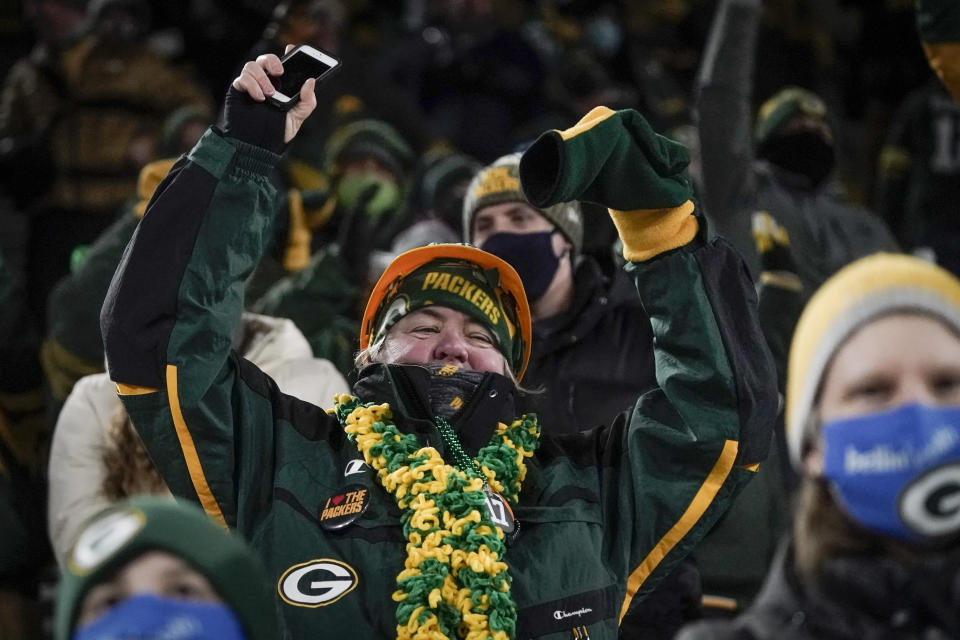 A spectator celebrates in the stands during the second half of an NFL divisional playoff football game between the Green Bay Packers and the Los Angeles Rams Saturday, Jan. 16, 2021, in Green Bay, Wis. (AP Photo/Morry Gash)