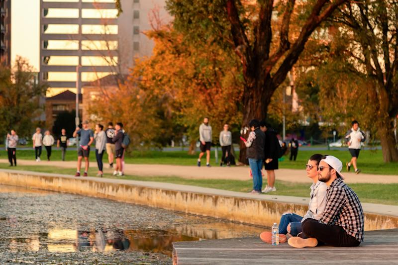 A couple sits by the edge of Albert Park Lake to watch the sunset as restrictions are being eased in Victoria.