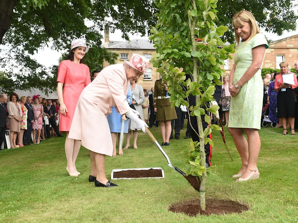 BELFAST, NORTHERN IRELAND - JUNE 24:  (EDITORIAL USE ONLY, NO SALES) In this handout image provided by Harrison Photography, Queen Elizabeth II pictured with the Secretary of State Theresa Villiers (L) planting a tree at a Garden Party in Hillsborough Castle on June 24, 2014 in Belfast, Northern Ireland. The Royal party are visiting Northern Ireland for three days.  (Photo by Simon Graham/Harrison Photography via Getty Images)