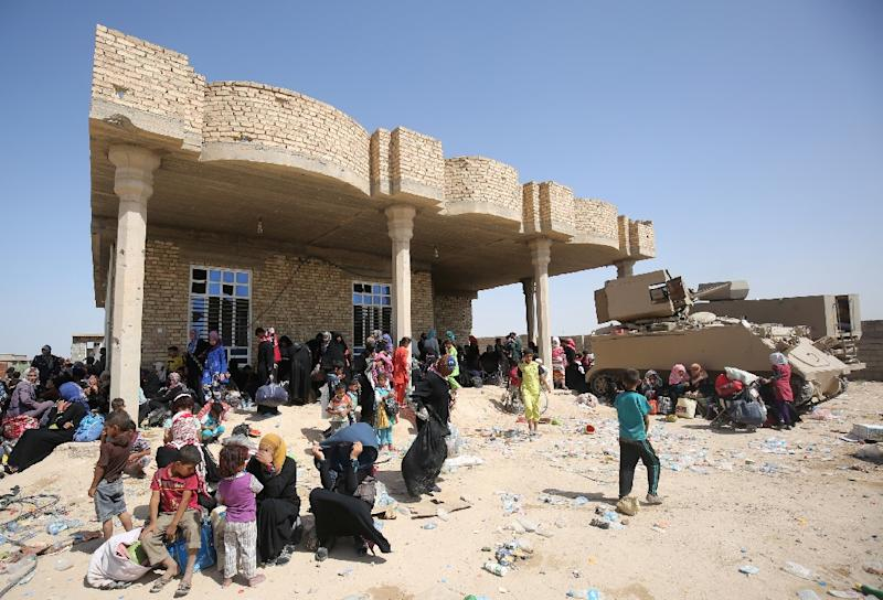 Iraqis who fled the violence in their village of Saqlawiyah, north west of Fallujah, wait to receive food and aid at a military point outside their village, on June 3, 2016