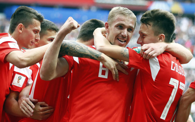 Russia's Yuri Gazinsky celebrates with teammates after scoring his side's first goal during the group A match between Russia and Saudi Arabia which opens the 2018 soccer World Cup at the Luzhniki stadium in Moscow, Russia, Thursday, June 14, 2018. (AP Photo/Matthias Schrader)