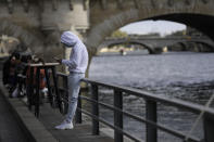 A man check his phone at a cafe terrace along the Seine river, Saturday Sept.26, 2020 in Paris. While France suffered testing shortages early in the pandemic, ramped-up testing since this summer has helped authorities track a rising tide of infections across the country. More than 15,000 new cases were reported Friday, and the Paris hospital system is starting to delay some non-virus surgeries to free up space for COVID-19 patients. (AP Photo/Lewis Joly)