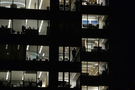 Workers continue working into the night in the City of London, Britain on October 16, 2017. Picture has been rotated 180 degrees. Picture taken October 16, 2017. REUTERS/Mary Turner