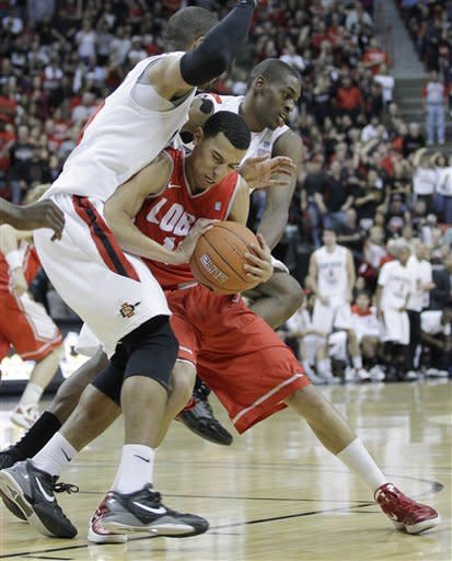 New Mexico's Kendall Williams, right, is fouled as he grabs a rebound by San Diego State's Tim Shelton in the first half of a semifinal NCAA college basketball game during the Mountain West Conference tournament, Saturday, March 10, 2012, in Las Vegas. (AP Photo/Julie Jacobson)