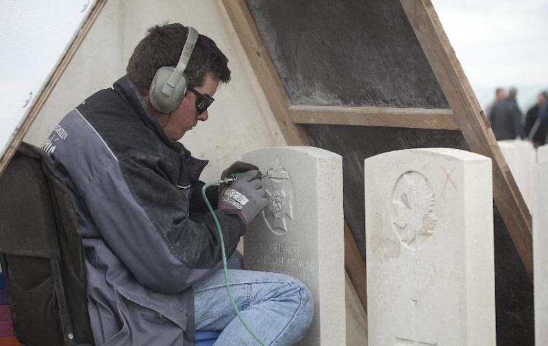 An engraver works under a rain tent as he re-engraves the headstone of a WWI soldier at Tyne Cot cemetery in Zonnebeke, Belgium on Monday, April 15, 2013. With nearly 12,000 graves the cemetery is the largest Commonwealth war cemetery in the world in terms of burials. Commonwealth cemeteries around the world are currently being renovated in preparation for centenary events which begin in 2014. (AP Photo/Virginia Mayo)
