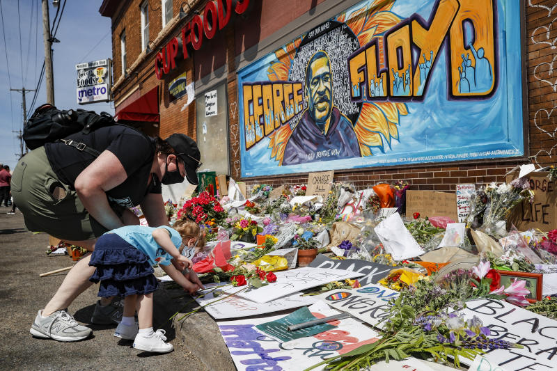 Jessica Knutson, and her daughter Abigail, 3, place flowers at a memorial to George Floyd, Sunday, May 31, 2020, in Minneapolis. Protests continued following the death of Floyd, who died after being restrained by Minneapolis police officers on May 25. (AP Photo/John Minchillo)