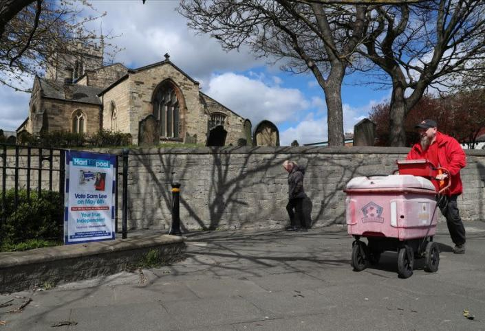 People walk past an election poster ahead of tomorrow's local elections, in Hartlepool