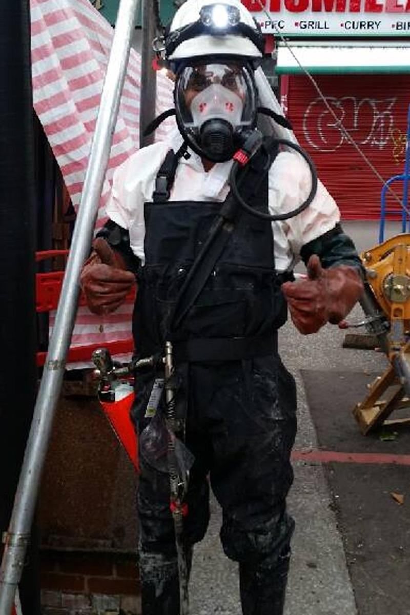 A workman in protective clothing prepares to go into the sewer to chip away at the enormous fatberg
