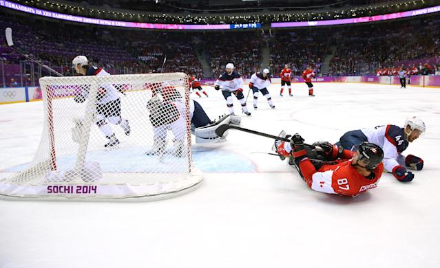 SOCHI, RUSSIA - FEBRUARY 21: Brooks Orpik #44 of the United States and Sidney Crosby #87 of Canada fall to the ice during the Men's Ice Hockey Semifinal Playoff on Day 14 of the 2014 Sochi Winter Olympics at Bolshoy Ice Dome on February 21, 2014 in Sochi, Russia. (Photo by Al Bello/Getty Images)