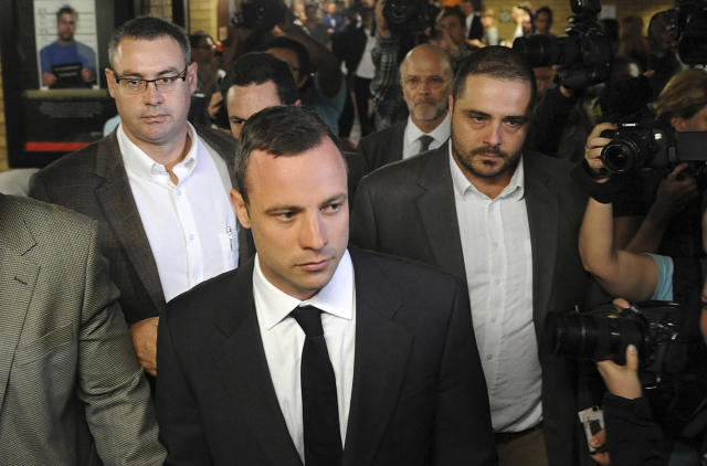 Oscar Pistorius, center front, arrives for his trial at the high court in Pretoria, South Africa, Monday, March 3, 2014. Pistorius is charged with murder with premeditation in the shooting death of girlfriend Reeva Steenkamp in the pre-dawn hours of Valentine's Day 2013. (AP Photo) SOUTH AFRICA OUT