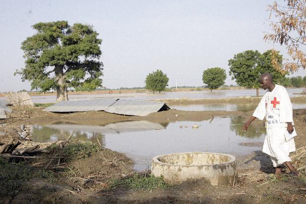 Man stands beside a well abandoned by villagers for fear of contamination after major flooding in Yakasawa village, Nigeria, on September 26, 2010
