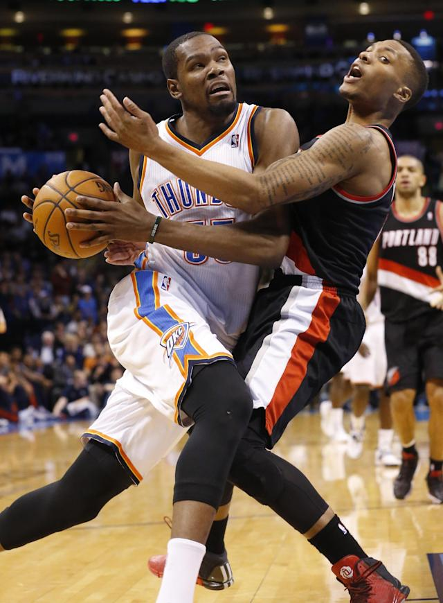Oklahoma City Thunder forward Kevin Durant, left, fouls Portland Trail Blazers guard Damian Lillard (0) as he drives to the basket in the fourth quarter of an NBA basketball game in Oklahoma City, Tuesday, Jan. 21, 2014. Oklahoma City won 105-97. (AP Photo/Sue Ogrocki)