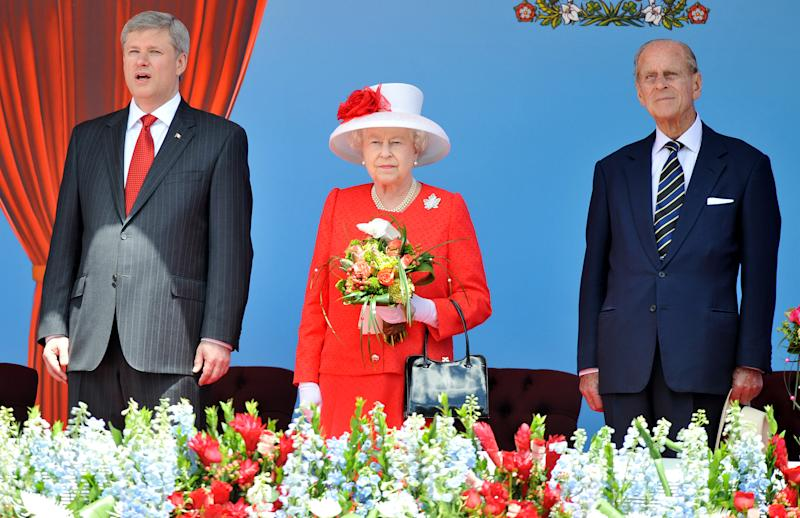 OTTAWA, ON - JULY 01: Queen Elizabeth II stands next to Canadian Prime Minister Stephen Harper and Prince Phillip, Duke of Edinburgh, in the Royal box outside the Canadian Parliament, during the Canada Day celebrations on July 1, 2010 in Ottawa, Canada. The Queen and Duke of Edinburgh are on an eight day tour of Canada starting in Halifax and finishing in Toronto. The trip is to celebrate the centenary of the Canadian Navy and to mark Canada Day. On July 6th the Royal couple will make their way to New York where the Queen will address the UN and visit Ground Zero. (Photo by John Stillwell-Pool/Getty Images)