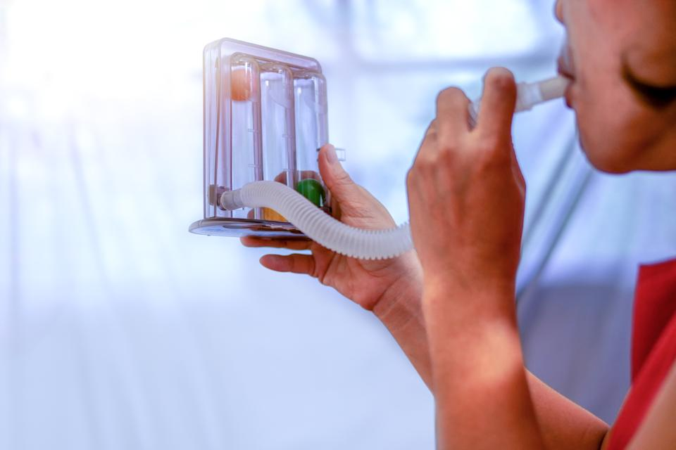 Close-Up Of Woman Using Spirometer