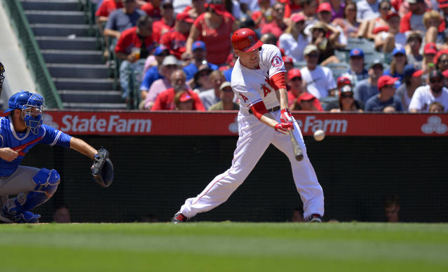 Los Angeles Angels' Mark Trumbo hits a three-run home run as Toronto Blue Jays catcher J.P. Arencibia looks on during the fourth inning of their baseball game, Sunday, Aug. 4, 2013, in Anaheim, Calif. (AP Photo/Mark J. Terrill)
