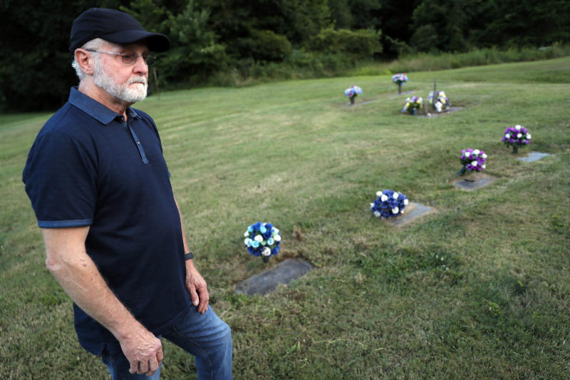 Eddie Davis stands beside the gravestone of his son Jeremy, furthest left, who died from the abuse of opioids, Wednesday, July 17, 2019, in Coalton, Ohio. Members of his family are buried in adjacent plots, including his parents and a sibling. (AP Photo/John Minchillo)