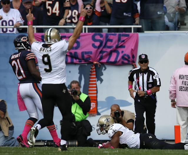 New Orleans Saints quarterback Drew Brees (9) celebrates as running back Pierre Thomas holds on to his ball in the end zone foe a touchdown during the first half of an NFL football game, Sunday, Oct. 6, 2013, in Chicago.(AP Photo/Charles Rex Arbogast)