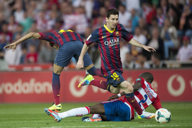 Barcelona's Lionel Messi from Argentina, center, in action with Granada's Allan Romero Nyom from France during a Spanish La Liga soccer match between FC Granada and FC Barcelona at Los Carmenes stadium in Granada, Spain, Saturday, April 12, 2014. (AP Photo/Daniel Tejedor)