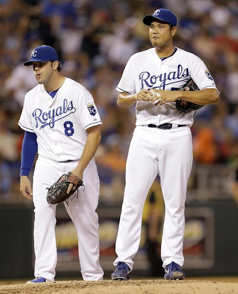 Kansas City Royals starting pitcher Bruce Chen, right, stands on the mound with third baseman Mike Moustakas (8) before Chen left the game during the sixth inning of a baseball game against the Cleveland Indians, Wednesday, Sept. 18, 2013, in Kansas City, Mo. (AP Photo/Charlie Riedel)