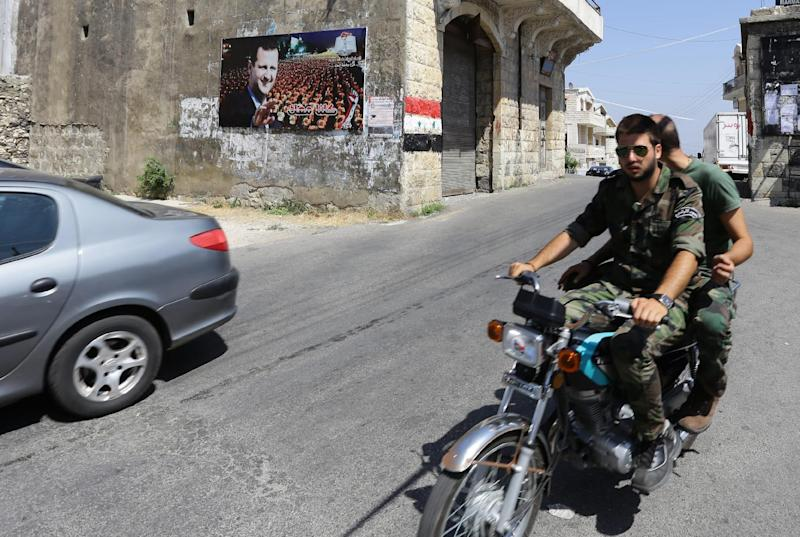 Two young Syrian soldiers ride a motorcycle past a huge poster bearing a portrait of President Bashar al-Assad next to a painting of a Syria's national flag in the Christian town of Marmarita in the central Homs region, on August 19, 2013