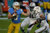 Los Angeles Chargers quarterback Justin Herbert (10) is under pressure by Miami Dolphins defensive back Nik Needham (40) and defensive end Emmanuel Ogbah (91) during the first half of an NFL football game, Sunday, Nov. 15, 2020, in Miami Gardens, Fla. (AP Photo/Wilfredo Lee)