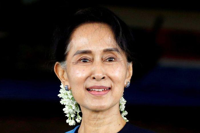 Aung San Suu Kyi smiling with white flowers in her hair