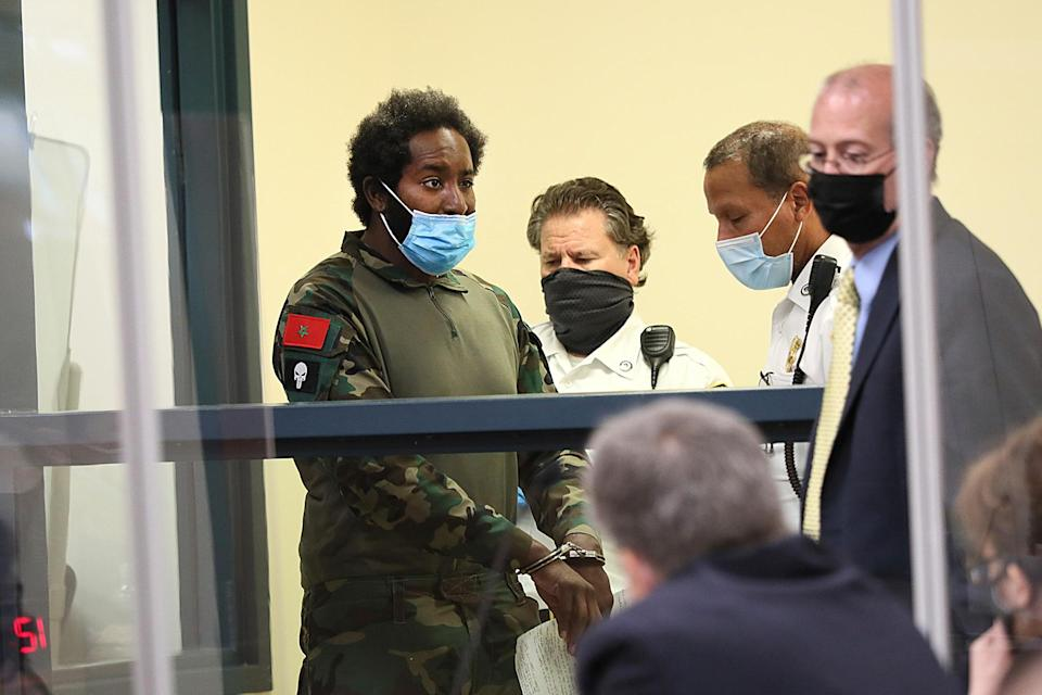 Quinn Cumberlander, left, one of 11 people charged in connection with an armed standoff along a Massachusetts highway last weekend, appears during his arraignment at Malden District Court, Tuesday, July 6, 2021, in Medford, Mass. (Suzanne Kreiter/The Boston Globe via AP, Pool)