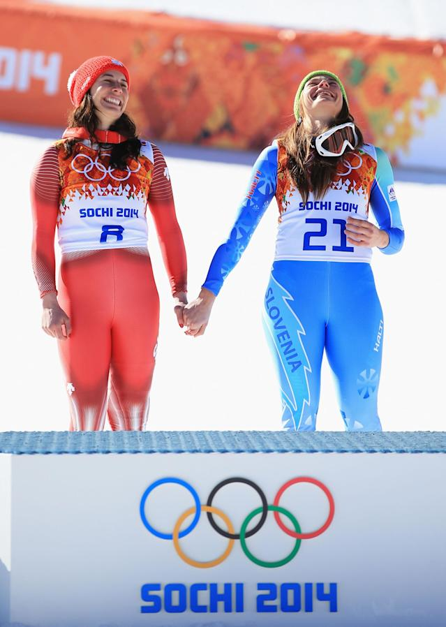 SOCHI, RUSSIA - FEBRUARY 12: Gold medalists Dominique Gisin of Switzerland (L) and Tina Maze of Slovenia hold hands during the flower ceremony for during the Alpine Skiing Women's Downhill on day 5 of the Sochi 2014 Winter Olympics at Rosa Khutor Alpine Center on February 12, 2014 in Sochi, Russia. (Photo by Richard Heathcote/Getty Images)