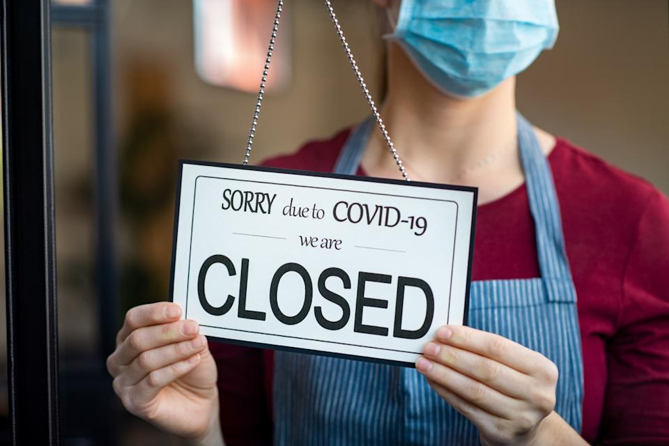 "Woman in mask holding ""closed"" sign"