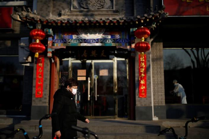 A woman wearing a face mask walks along the street as the country is hit by an outbreak of the new coronavirus, in Beijing