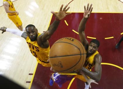 LeBron James and Tristan Thompson reach for a common goal. (Larry W. Smith-Pool/Getty Images)