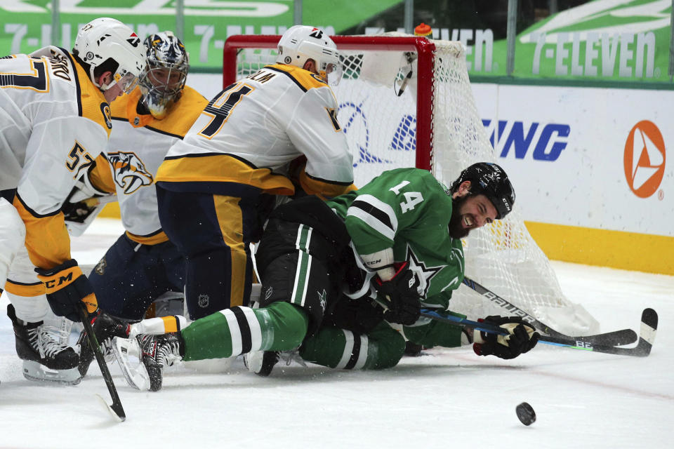 Dallas Stars left wing Jamie Benn (14) gets knocked to the ice by Nashville Predators defenseman Mattias Ekholm (14) while trying to score in the second period during an NHL hockey game on Sunday, March 7, 2021, in Dallas. (AP Photo/Richard W. Rodriguez)