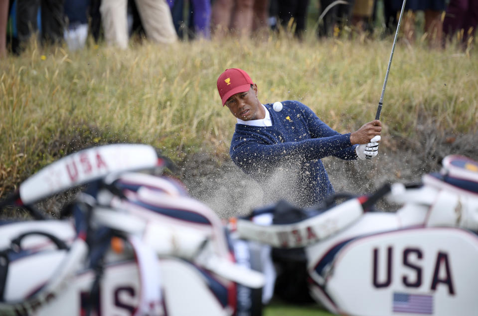 USA captain Tiger Woods hits out of a bunker during a practice session ahead of the President's Cup Golf tournament in Melbourne, Tuesday, Dec. 10, 2019. (AP Photo/Andy Brownbill)