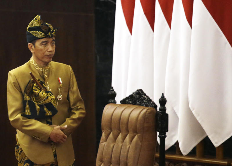 Indonesia's President Joko Widodo in Nusa Tenggara Barat traditional dress, stands after delivers his state of the nation address ahead of the country's Independence Day at the parliament building in Jakarta, Indonesia, Friday, Aug. 16, 2019. Widodo has appealed support to move the country's capital outside of its most populous island, Java, in an annual national address.(AP Photo/Achmad Ibrahim)