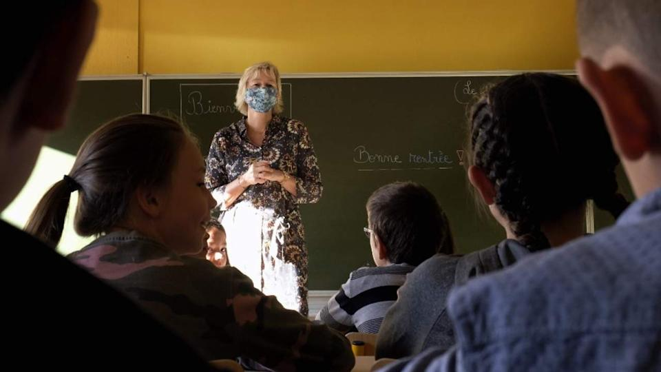 Pupils listen to a teacher wearing a mask in the classroom in a school in Helecine, Belgium on 1 September 2020, on the first day of school year amid the Covid-19 epidemic. AFP