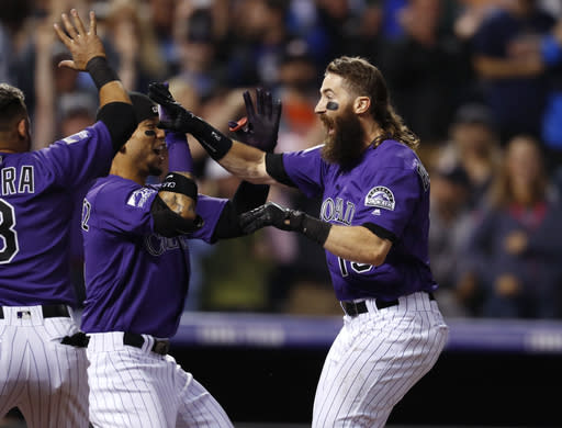 Colorado Rockies' Gerardo Parra, left, and Carlos Gonzalez, center, welcome Charlie Blackmon as he crosses home plate after hitting a walk-off solo home run off Houston Astros relief pitcher Collin McHugh in a baseball game Wednesday, July 25, 2018, in Denver. The Rockies won 3-2. (AP Photo/David Zalubowski)